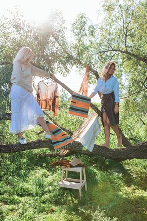 Portrait of two beautiful women brunette and blond standing on the big brunch of tree in a field in late summer. Beautiful girls standing next to each other.
