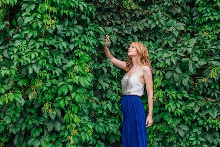 Portrait of a young beautiful woman, standing next to the wall of wild grape leaves.