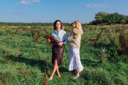 Portrait of two beautiful women in a field in late summer. Beautiful girls standing next to each other and holding bouquet made of dry brown plants. 写真素材