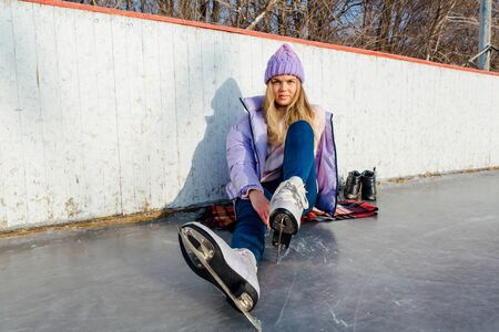 Lovely young woman sitting on ice ring and tieing shoelaces
