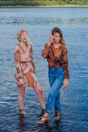 Two pretty sisters standing in river next to the shore on a cloudy windy summer day, having fun and laughing.