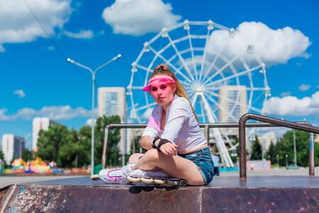 Portrait of an emotional girl in a pink cap visor wearing protective gloves  ,sitting on the background of ferris wheel and relaxing.