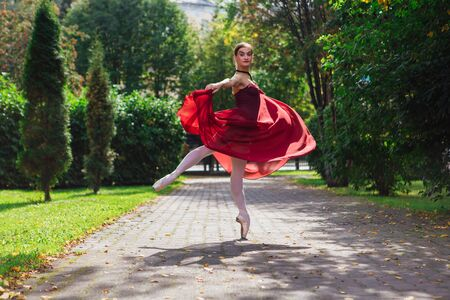 Woman ballerina in red ballet dress dancing in pointe shoes in autumn park. Ballerina standing in beautiful ballet pose