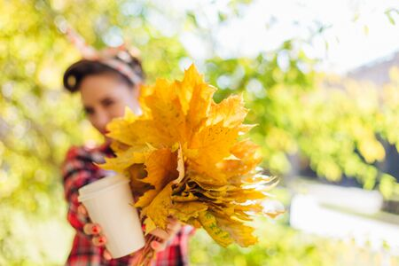 Beautiful woman with make up and hair in pin up holding big bouquet of maple yellow leaves and white cup of coffee to go in a sunny autumn day. Copy space.