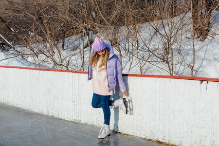 Lovely young woman riding ice skates on the ice rink. Girl skating on ice in a winter frosty day
