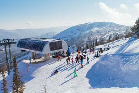 Dki lift on the top of the snowy mountain in winter. Many people on slope 版權商用圖片