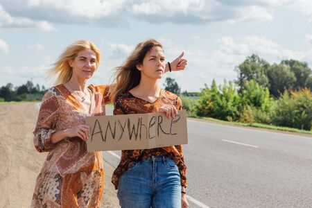 Two beautiful hippy girls hitchhiking and vote with a sign ANYWHERE on road. Copy space.