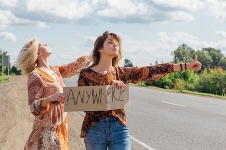 Two beautiful hippy girls hitchhiking and vote with a sign ANYWHERE on road. Copy space. Archivio Fotografico