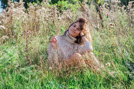 Happy young beautiful woman dressed in a sweater and underpants sitting in a field of dry agrimony.