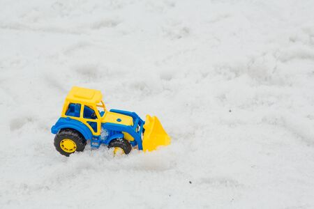 Toy plastic loader on a wet melting snow. A fun game in winter time for kids. Copy space