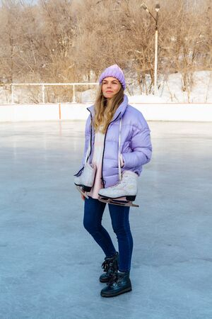 Lovely young woman with ice skates hanging on neck on the ice rink. Girl is going to skating on ice in a winter frosty day Stok Fotoğraf