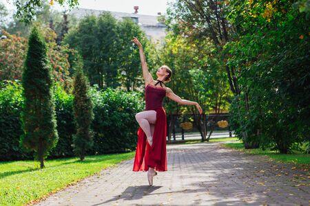 Woman ballerina in red ballet dress dancing in pointe shoes in autumn park. Ballerina standing in beautiful ballet pose Foto de archivo - 138775183