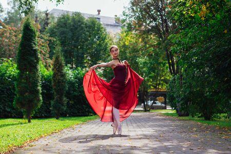 Woman ballerina in red ballet dress dancing in pointe shoes in autumn park. Ballerina standing in beautiful ballet pose Foto de archivo - 138724203