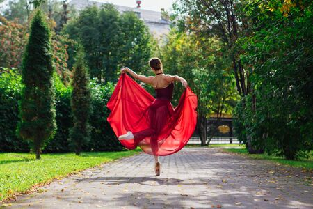 Woman ballerina in red ballet dress dancing in pointe shoes in autumn park. Ballerina standing in beautiful ballet pose Foto de archivo - 138724437