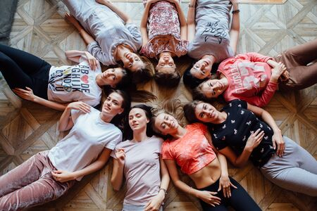 Top view of nine happy beautiful women laying on the floor poding and smiling. Pajama party