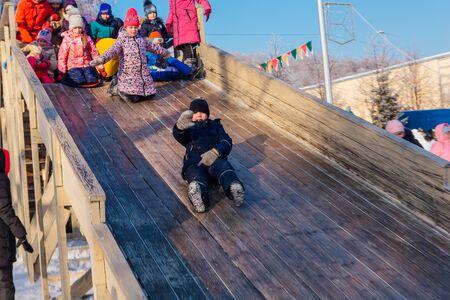 Novokuznetsk, Russia- January 07, 2019: Russian winter entertainment: children having fun tobogganing from wooden toboggan in a frosty winter day