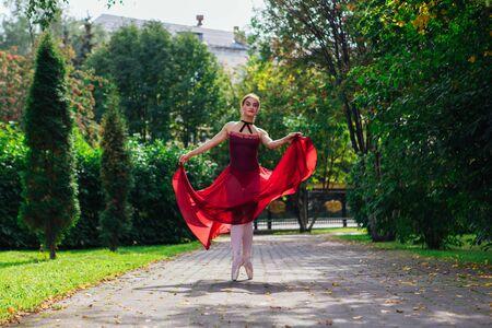 Woman ballerina in red ballet dress dancing in pointe shoes in autumn park. Ballerina standing in beautiful ballet pose Foto de archivo - 138725571