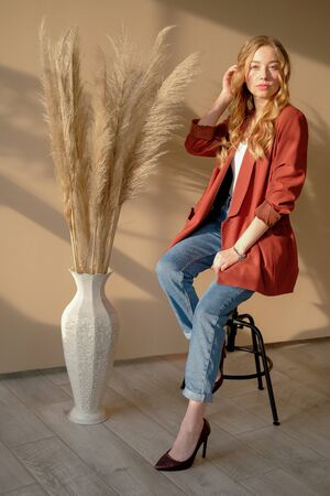 Young beutiful blond woman wearing brown jacket and blue jeans sitting on bar chair in a daylight from window. Girl sitting on the beige background next to the vase with dry plants.