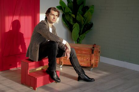 Tall handsome man wearing white t-shirt and brown jacket sitting on the red stairs next to green plant and wooden box. Man sitting in a daylight from the window. Copy space