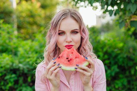 Beautiful young woman with pink hair enjoying sweet juicy watermelon