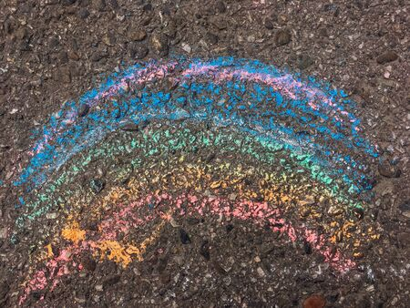 Rainbow drawn by child with chalks on the asphalt surface.