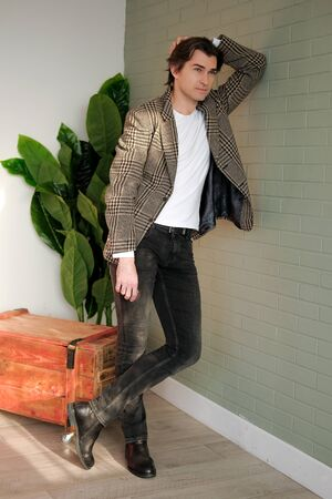 Tall handsome man wearing white t-shirt and brown jacket standing next to grey wall. Man standing in a daylight from the window. Copy space