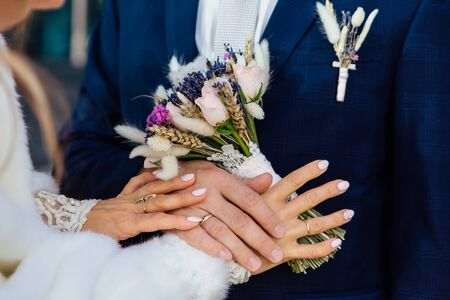 Hands of the bride and groom on the wedding bouquet Imagens