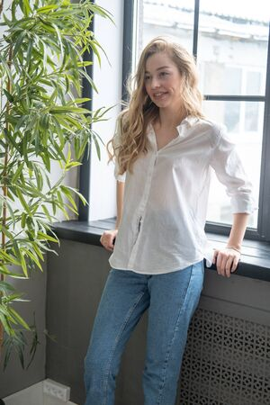 Young beutiful blond woman wearing white shirt and blue jeans standing next to window. Morning portrait of a girl with window and green plants on the background