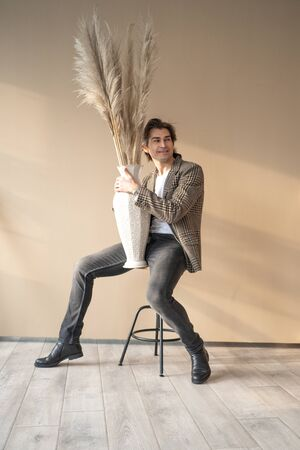 Tall handsome man wearing brown jacket sitting on bar chair in a daylight from window. Man sitting on the beige background holding vase with dry plants. Banque d'images