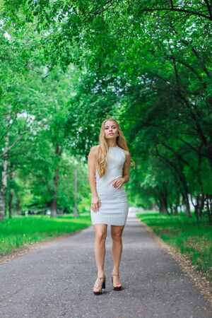 Spring portrait of a charming blond woman wearing beautiful white dress standing on the road under green trees. Banque d'images