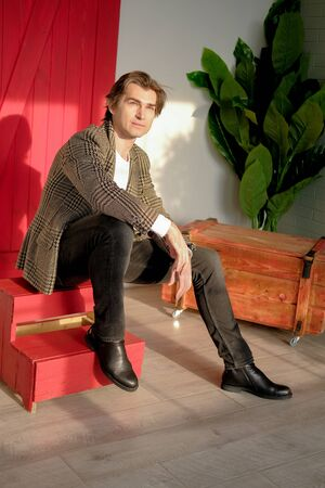 Tall handsome man wearing white t-shirt and brown jacket sitting on the red stairs next to green plant and wooden box. Man sitting in a daylight from the window.