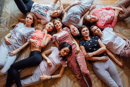 Top view of nine happy beautiful women laying on the floor. Фото со стока