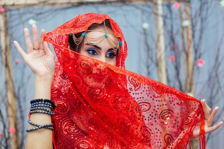 Close up portrait of a beautiful eastern woman with bright makeup and jewelry wearing red headscarf.
