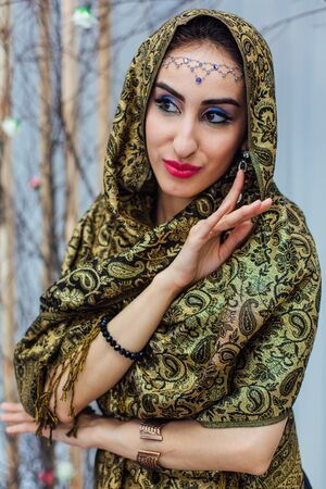 Close up portrait of a beautiful eastern woman with bright makeup and jewelry wearing headscarf.