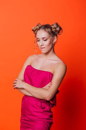 The girl in a red dress on a orange background in the studio. Blonde girl with two hair knots looking to the camera and smiling.