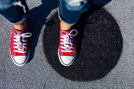 Red sneakers shoes on woman's feet on the asphalt with black circle. Sneakers shoes Couple. Copy space. Foto de archivo