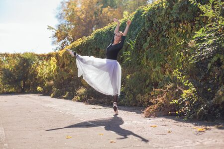 Woman ballerina in a white ballet skirt dancing in pointe shoes in a golden autumn park. Ballerina standing in beautiful ballet pose Foto de archivo