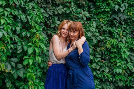 Beautiful mother and her grown up daughter hugging each other on a summer day outside on a green nature background Foto de archivo