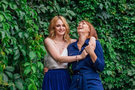 Beautiful mother and her grown up daughter hugging each other and laughing on a summer day outside on a green nature background