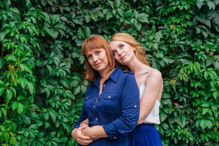 Beautiful mother and her grown up daughter hugging each other on a summer day outside on a green nature background Stock Photo