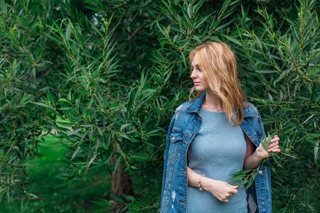 Portrait of a young beautiful woman with make up and curly blond hair dressed in jeans jacket, standing next to the tree with green leaves in a windy weather. Copy space.