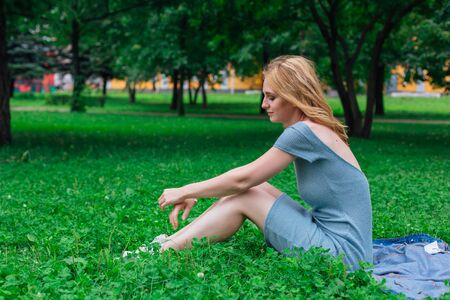 Portrait of a young beautiful woman with make up and curly blond hair, sitting on the green grass in city park. Copy space.