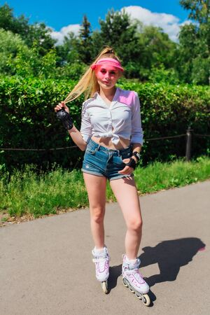 Portrait of an emotional beautiful young girl in a pink cap visor and protective gloves for rollerskate Foto de archivo