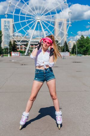 Portrait of an emotional beautiful young girl in a pink cap visor and protective gloves for rollerskate Stock Photo