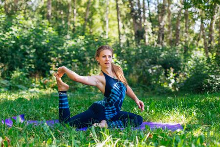 Young caucasian woman doing yoga exercises in summer city park. Stock Photo