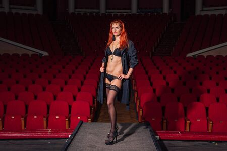 Full length portrait of a woman in black underware and a coat standing on theatre stage with red seats on the background
