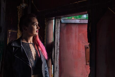 Portrait of a young girl with pink hair dressed in leather jacket standing next to the old rusty door inside of collapsed building. Reklamní fotografie