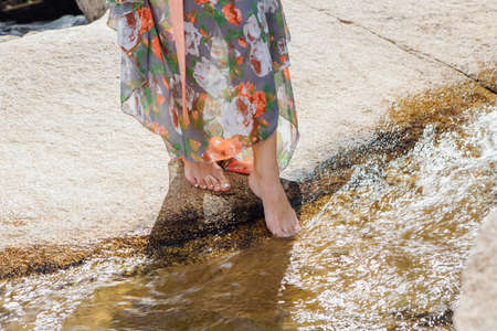 Woman with bare feet standing next to the running river