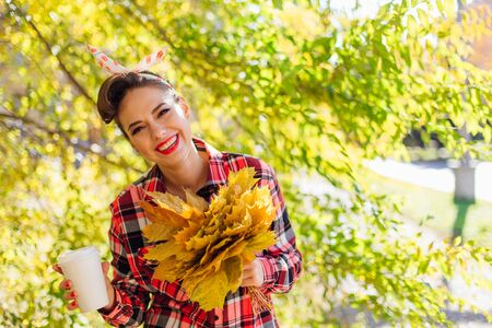 Beautiful woman with make up and hair in pin up style holding big bouquet of maple yellow leaves and white cup of coffee to go in a sunny autumn day. Copy space.