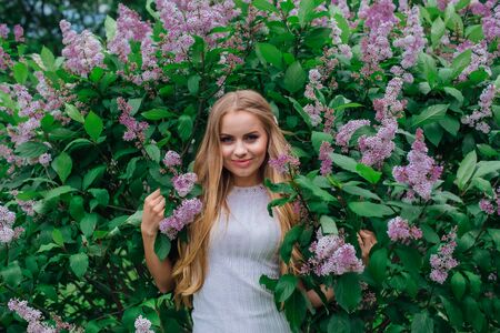 Spring portrait of a charming blond woman wearing beautiful white dress standing next to blooming purple lilac bush.